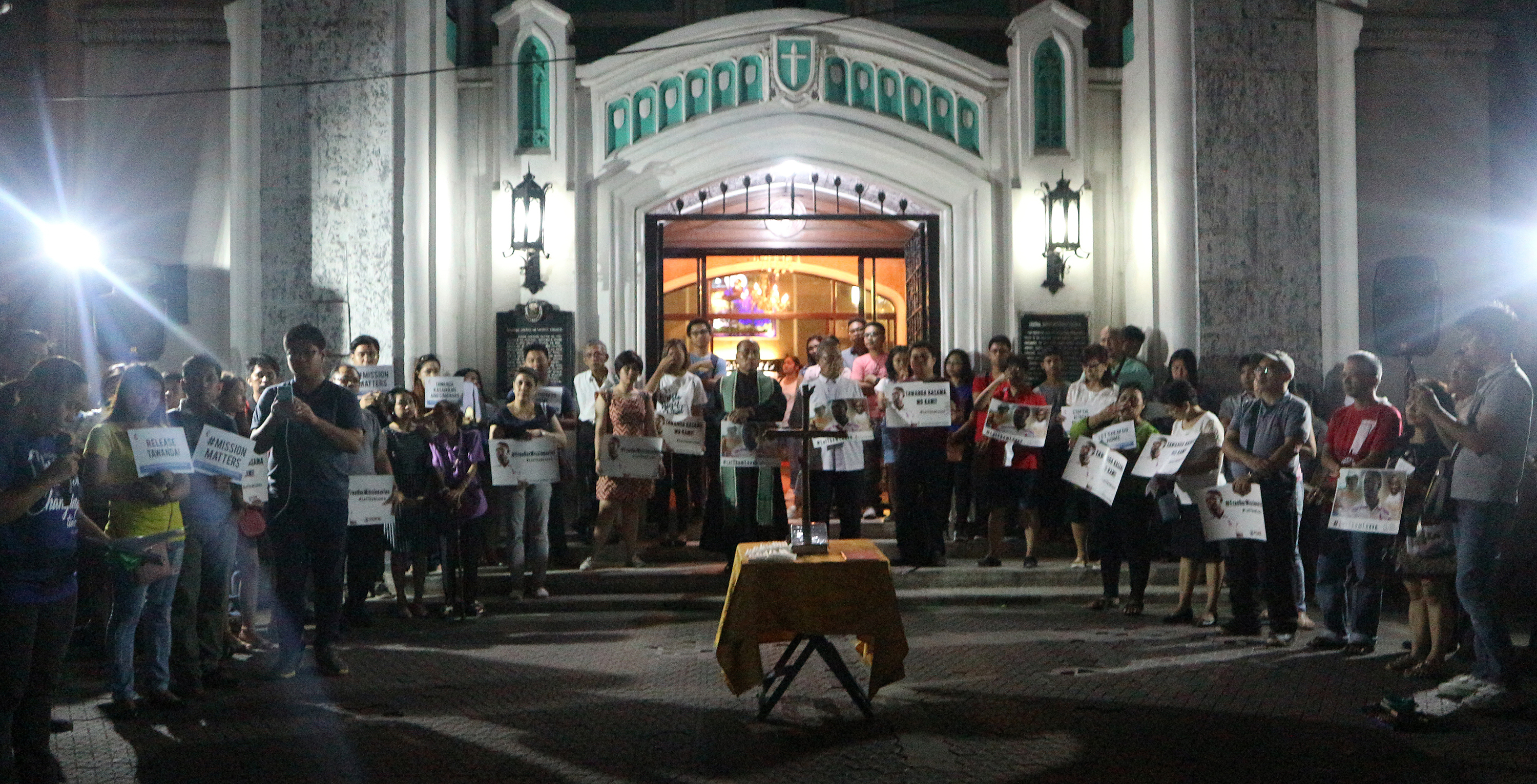 A crowd holds signs outside Central United Methodist Church in Manila in support of the missionaries from the United Methodist Board of Global Ministries detained by the Philippine's government. Photo courtesy of Gladys Mangiduyo, UMNS.