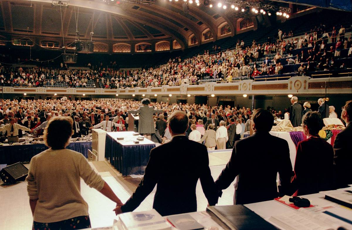 Delegates and guests to the United Methodist Church's 2000 General Conference join hands in song during a break in conference proceedings caused when people protesting the church's anti-homosexual policies blocked the aisles. A UMNS photo by John C. Goodwin
