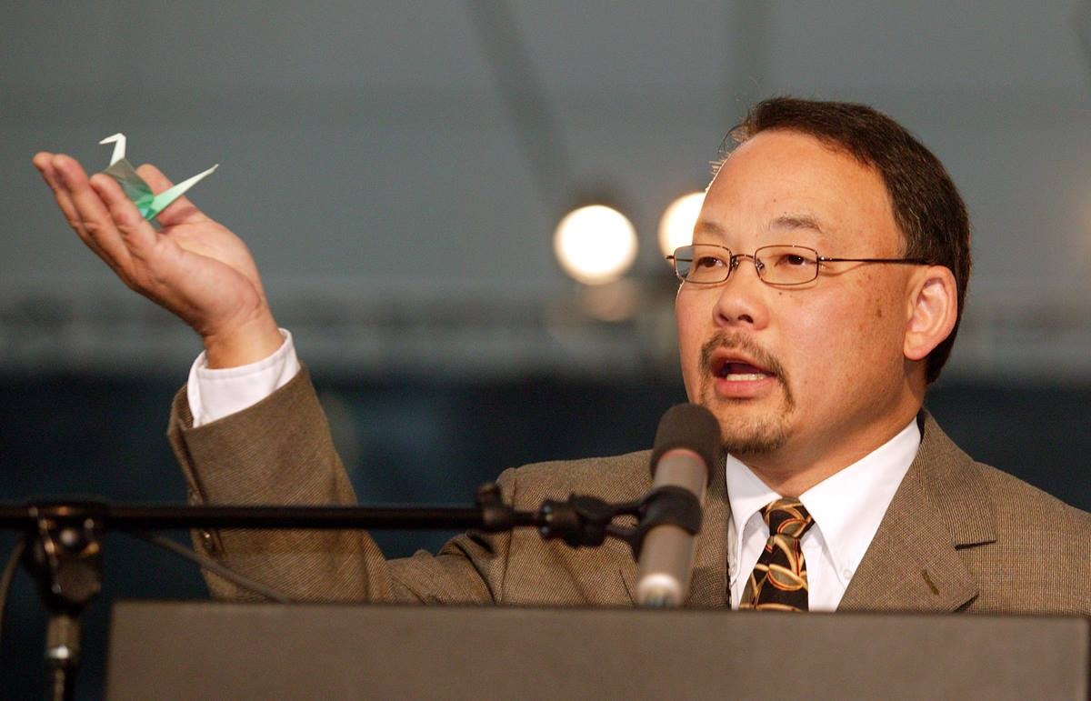 The Rev. Bob Hoshibata holds an origami paper crane, one of about 1,000 that members of the Pacific Northwest delegation to the United Methodist Church's 2004 General Conference folded as prayers for peace. A UMNS photo by Mike DuBose.