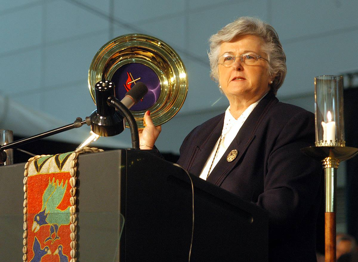 Sandra Kelley Lackore, top staff executive of the United Methodist Church's General Council on Finance and Administration, uses a church offering plate to emphasize the resources for mission and ministry as she discusses the financial state of the church during the denomination's 2004 General Conference in Pittsburgh. A UMNS photo by John C. Goodwin.
