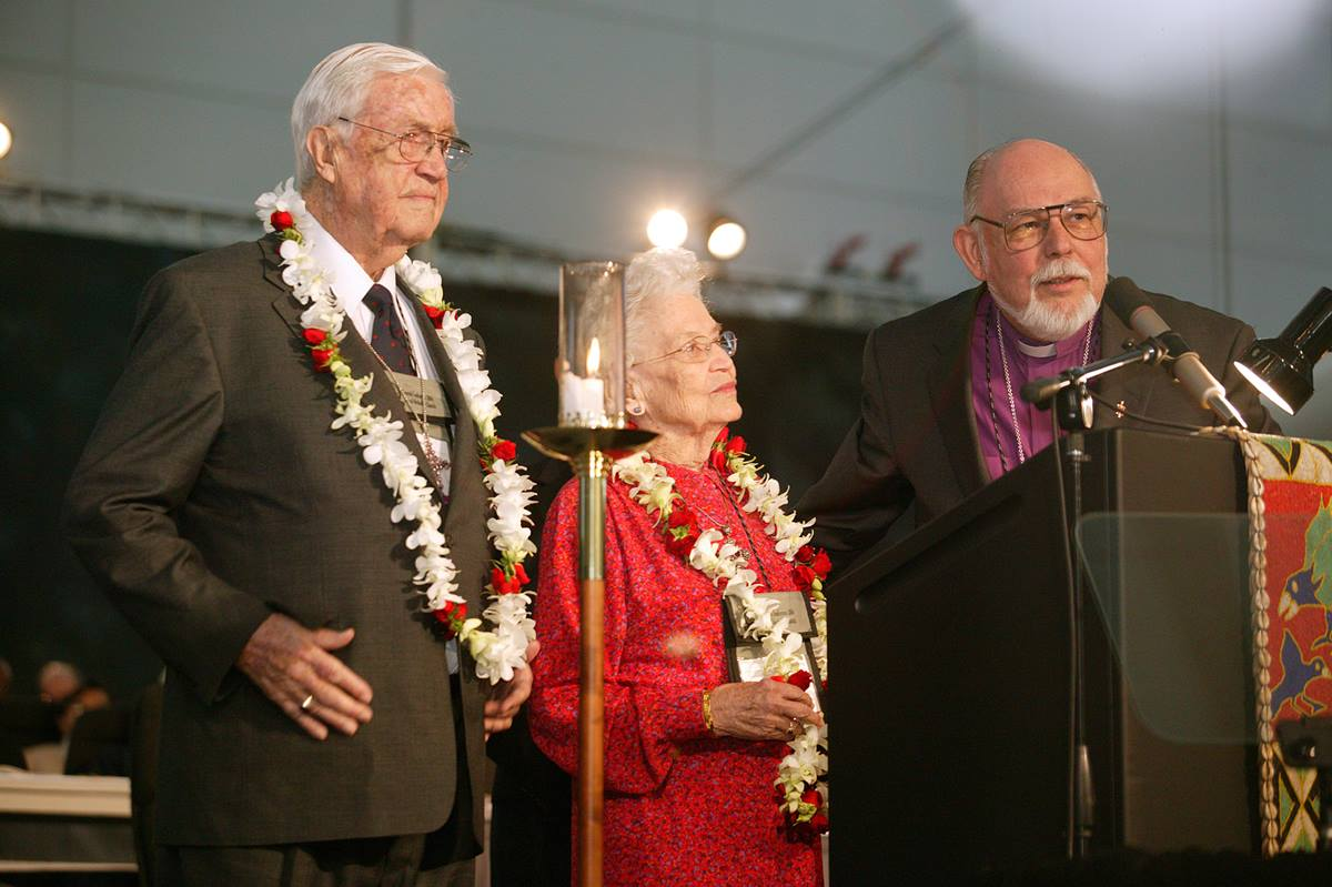 United Methodist Bishop Joel N. Martinez (right), president of the General Board of Global Ministries, honors Eunice Mathews during a session of the denomination's 2004 General Conference in Pittsburgh. The tribute on Mrs. Mathews' 90th birthday recognized her lifetime of service to the church. Those honoring her include her husband, Bishop James K. Mathews. A UMNS photo by Mike DuBose.