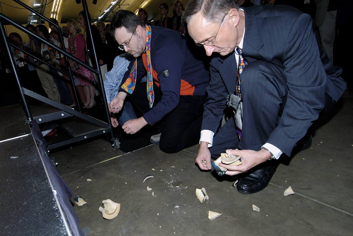 "Bishop Donald A. Ott (right) picks up pieces of a communion chalice intentionally broken during a protest after delegates to the 2004 United Methodist General Conference in Pittsburgh maintained language in the church's Book of Discipline that the practice of homosexuality is ""incompatible with Christian teaching."" A UMNS photo by Paul Jeffrey."