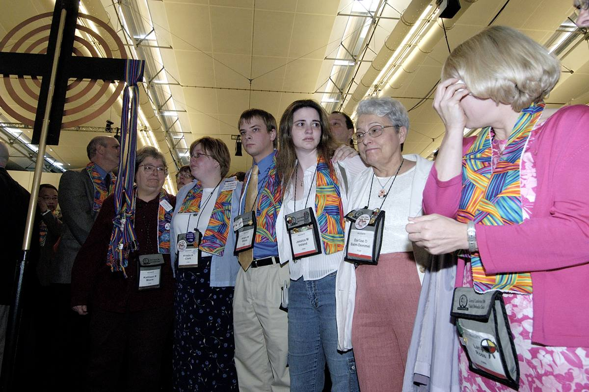 """Supporters of gay men and lesbians mourn after delegates to the 2004 United Methodist General Conference in Pittsburgh voted to maintain language in the church's Discipline that the practice of homosexuality is """"incompatible with Christian teaching."""" Many wearing multicolored scarves, those who supported gays and lesbians remained standing throughout the debate and votes. A UMNS photo by Paul Jeffrey."""