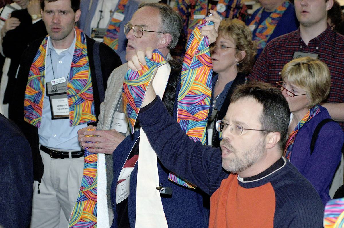 Supporters of wording that would say Christians are not of one mind about the incompatibility of the practice of homosexuality with Christian teaching speak out in protest after delegates to the 2004 United Methodist General Conference in Pittsburgh voted to maintain language in the denomination's Book of Discipline. Many wearing multicolored scarves stood in support of gay men and lesbians throughout the debate and votes. A UMNS photo by Paul Jeffrey