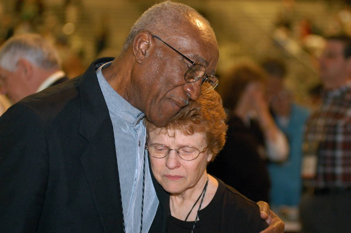 Delegates Burnham A. Robinson (left) and Rev. Judith A. Sands, both from Central Texas, embrace following a vote of the 2004 General Conference in Pittsburgh affirming unity in the United Methodist Church. The overwhelming approval of the resolution on unity followed several days of contentious debate on the issues in the church related to homosexuality. A UMNS photo by John C. Goodwin.