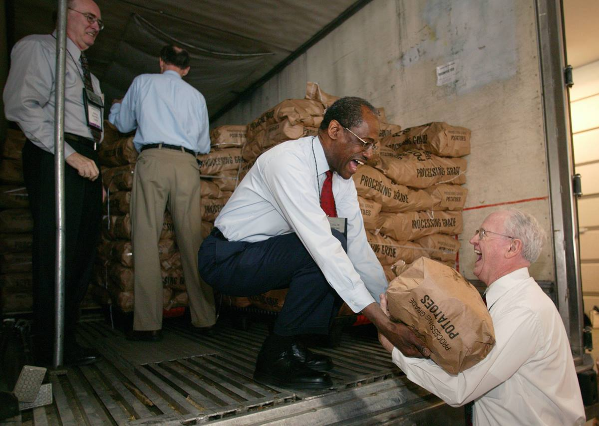 Bishops Ernest S. Lyght (kneeling) and Raymond Owen (right) share a laugh while helping to unload 45,000 pounds of potatoes. A UMNS photo by Mike DuBose.