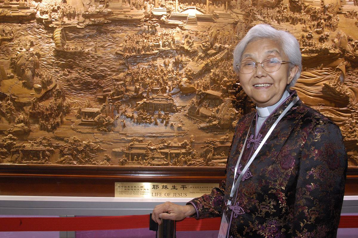 "The Rev. Cao Sheng-jie, president of the China Christian Council, stands next to a giant wood carving that is part of the ""A Lamp to My Feet, A Light to My Path,"" a Bible ministry exhibition from China.  A UMNS photo by John Goodwin."