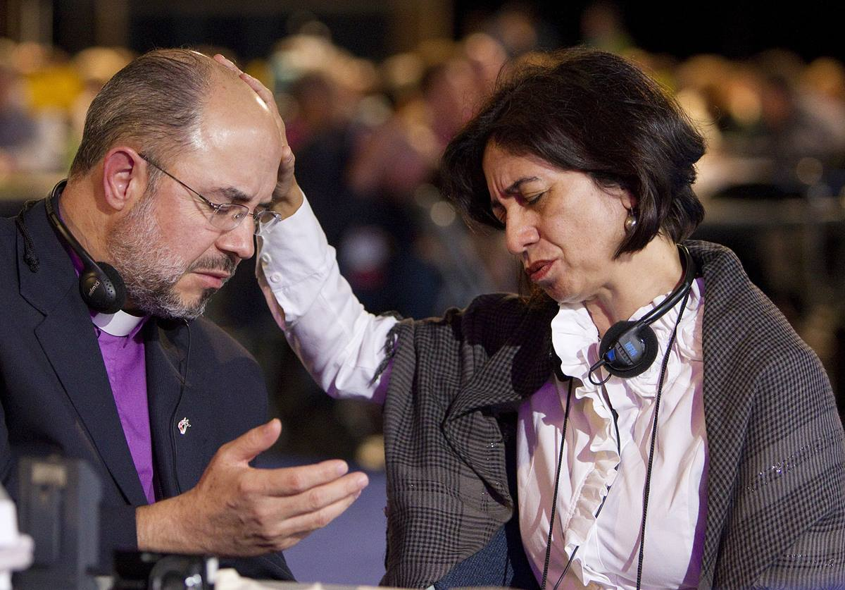 Bishop Marisa de Freitas Ferreira (right) of the Methodist Church of Brazil prays for Bishop Adonias Pereira do Lago, also of Brazil, during evening worship at the 2012 United Methodist General Conference in Tampa, Fla