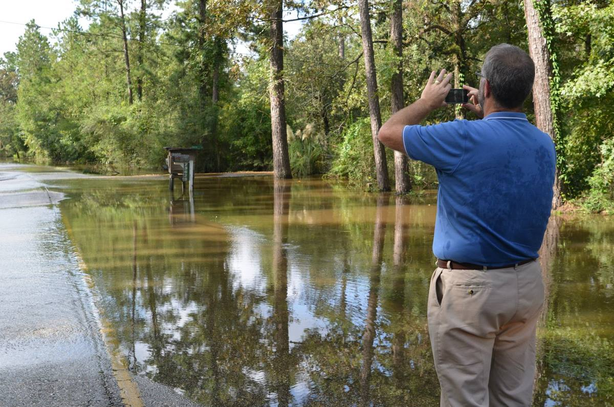 The Rev. Tom Hazelwood of the United Methodist Committee on Relief takes pictures of the flooded road leading to Lee's Landing United Methodist Church.