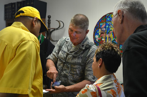 The Rev. Tim Neustifter, a chaplain and lieutenant colonel in the Louisiana Air National Guard, shows the conference assessment team photos he took of flooded areas near Belle Chasse, La.