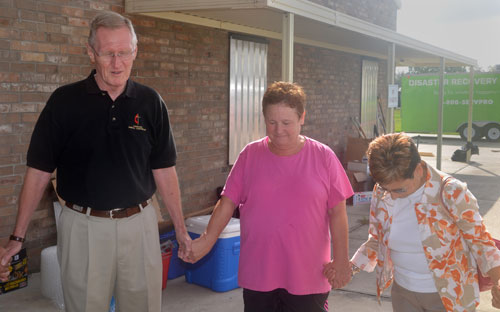 The Rev. Don Cottrill and Bishop Cynthia Fierro Harvey (right) pray with the Rev. Regina Hickman in front of First United Methodist Church in LaPlace, La. The church had a foot of standing floodwater during Hurricane Isaac. Photos courtesy of Betty Backstrom.