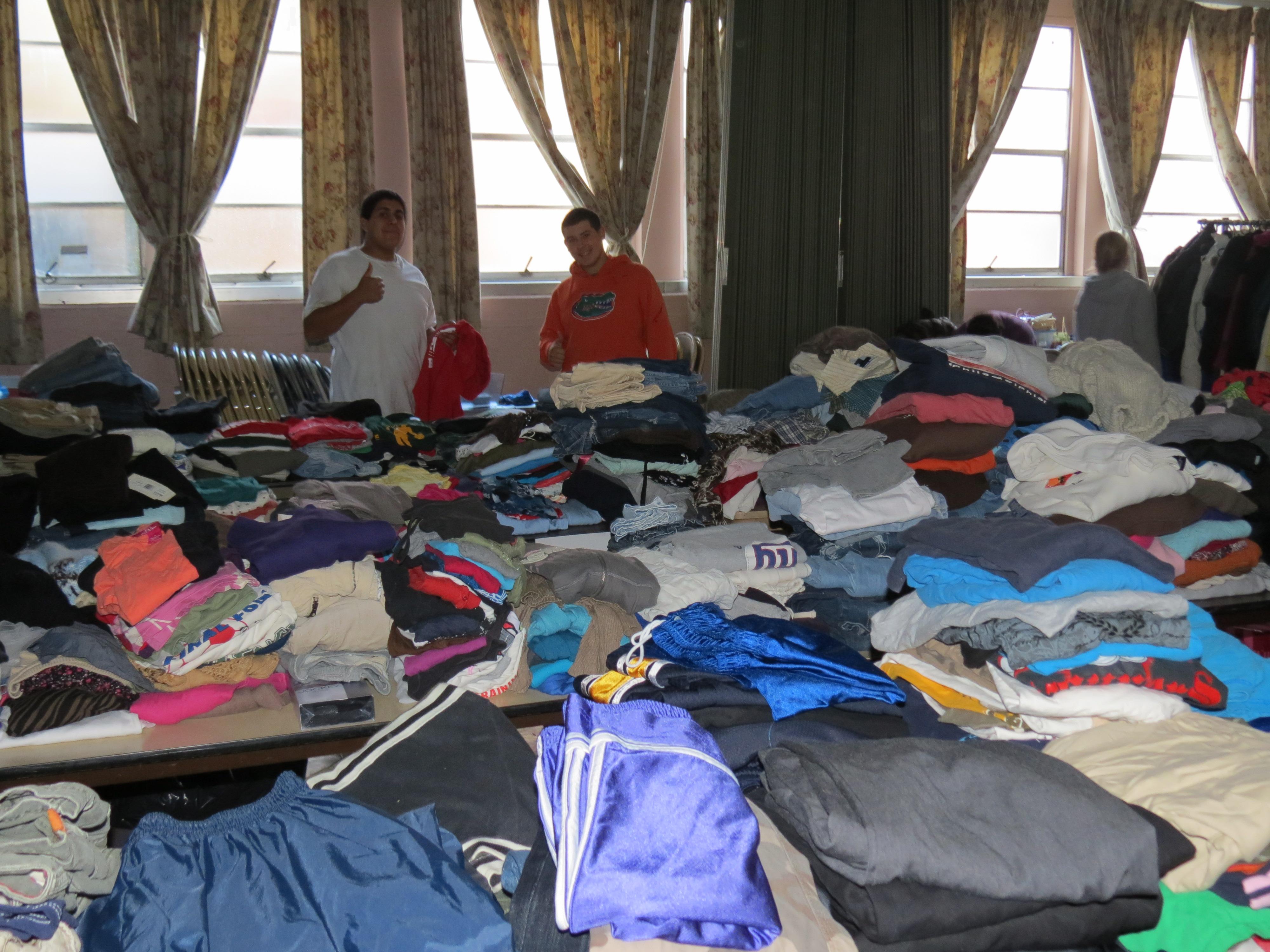 Teen volunteers sorting donated clothing in the dark basement of Grace UMC in Lindenhurst, N.Y.