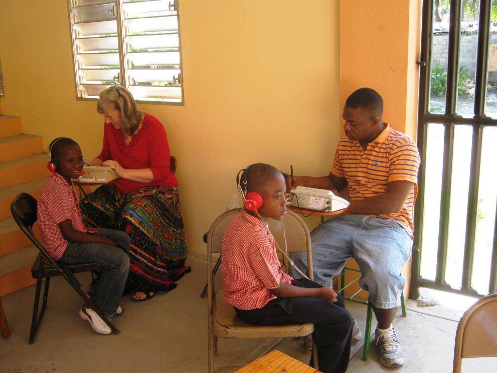 Dr. Sally Muhlbach and Dr. Ricardo Gautier test the hearing of Haitian school children. Photo by Gil Hanke