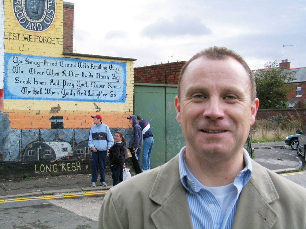 The Rev. Gary Mason, minister at the East Belfast Mission, stands in front of militaristic mural being painted over with an image that celebrates local culture and achievements. A 2003 UMNS file photo by Kathleen LaCamera