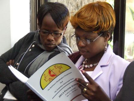 The Revs. Josephine Bangure and Tivai Mudzengerere go through the Pastors' School booklet.UMNS web-only photo by Taurai Emmanuel Maforo.