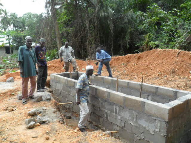 Workers construct new public toilets as part of a church-led community development project in Yonibana, Sierra Leone.