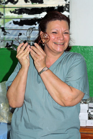 Jean Arnwine displays several pairs of glasses during a light moment at the Haiti Eye Clinic in Petit-Goâve, Haiti.