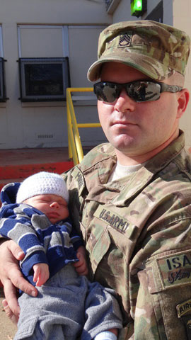 Army Staff Sgt. Joe Murray holds his 3-week-old baby at his Fort Campbell, Ky., battalion headquarters.Photo by Hope Murray
