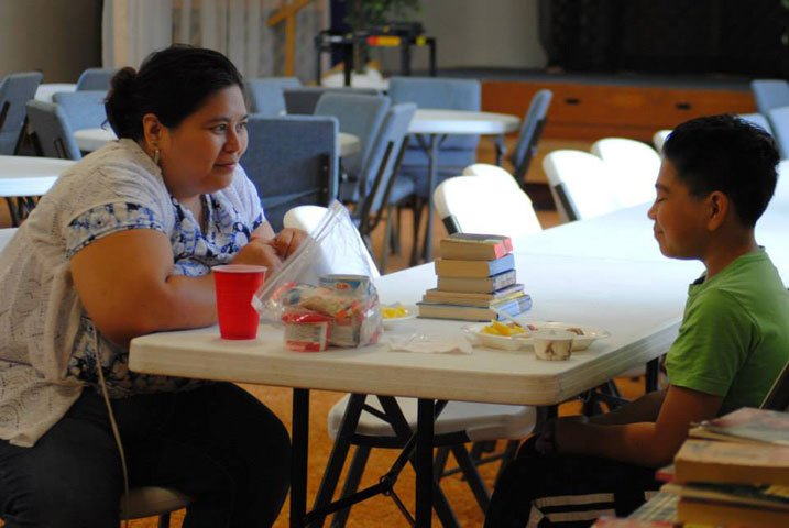 Adrian Perez and her son, Jonathan, enjoy an afternoon that includes a free lunch in the Havelock Cafe, picking up books for summer reading and selecting snacks and breakfast foods for the week. Photo courtesy of Delaney Fischer.