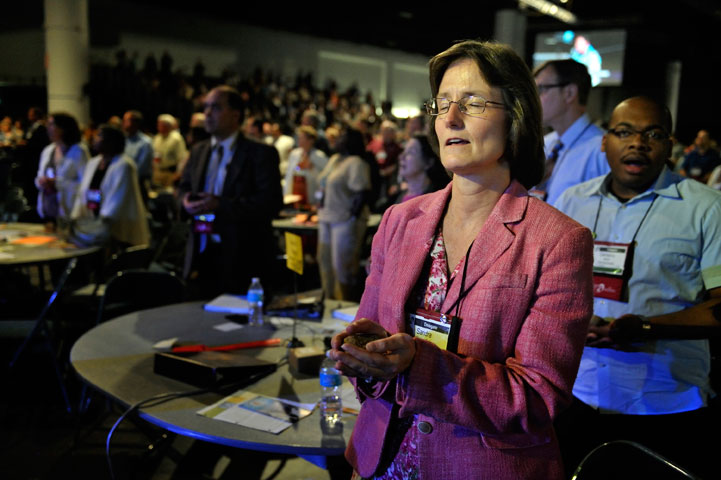 The Rev. Sandra Steiner Ball, now bishop of the West Virginia Episcopal Area, holds a stone as she prays during the Act of Repentance at the 2012 General Conference.