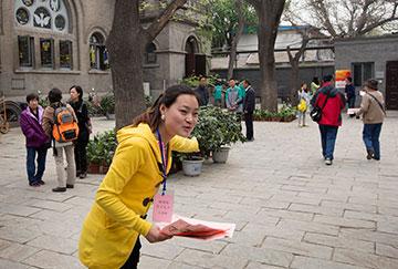 Greeter Wang Yan Na welcomes parishioners and visitors to Chongwenmen Church in Beijing.