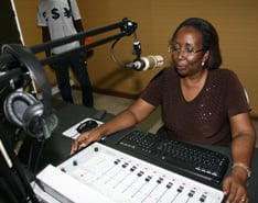 Acquah, director of the new 101.6 FM station, demonstrates the production studio equipment.
