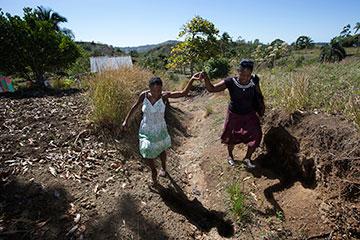 Yolande Gabriel (right) helps expectant mother Dieula Alrich make her way along a rural trail near Mizak, Haiti.