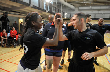 (From left) An army coach and player celebrate victory following a volleyball game played in recognition of Warrior Care Month. A UMNS photo by Jay Mallin.