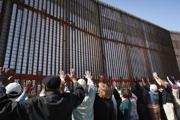 United Methodist bishops raise their hands in prayer in El Faro Park on the Mexican side of the border fence in Tijuana during the May 7 immersion experience.