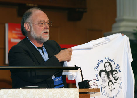 The Rev. David Farley, pastor of Echo Park United Methodist Church in Los Angeles, holds T-shirt bearing the likeness of immigrants in sanctuary around the country at an April 25 press conference hosted by the United Methodist Task Force on Immigration.