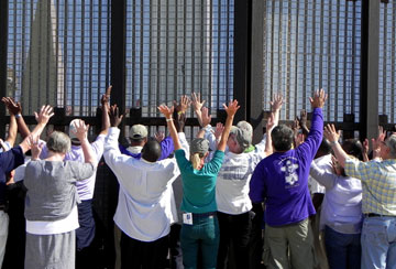 United Methodist bishops raise their arms in prayer next to the border fence in San Diego's Friendship Park. Other bishops do the same on the opposite side of the fence in Tijuana's El Faro Park. A UMNS photo by Karen Clark Ristine.