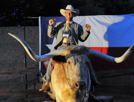 """Solomon Christian gets his photo made atop a long-horned steer at """"The Stars at Night, a Taste of Texas"""" reception April 27 at the Fort Worth Convention Center, site of the 2008 United Methodist General Conference."""