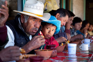 People of many ages share a community meal in San Miguel Huautla, Oaxaca, Mexico. Young people in rural areas of Mexico like this one often choose to emigrate to the United States and work for a few years because there are few opportunities at home.