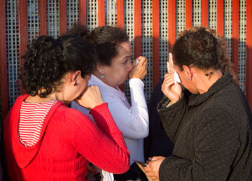 Mothers who are separated from their families in the U.S. cry at the Mexican side of the border wall between San Diego and Tijuana, Mexico, during the Posada Without Borders.
