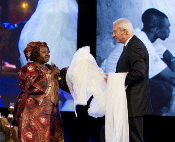 Here Gbanga and Bishop Thomas J. Bickerton hold an insecticide-treated mosquito net during a celebration of the work of the Imagine No Malaria campaign during the 2012 United Methodist General Conference in Tampa, Fla. A UMNS photo by Mike DuBose.