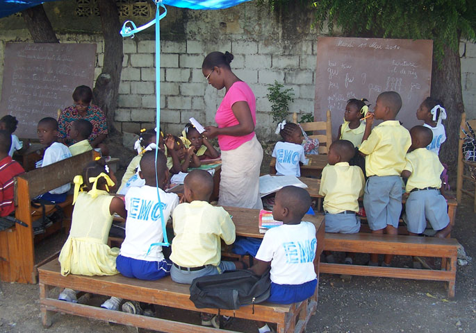 Children attend school under a tarp at the Carrefour Methodist church in Haiti.