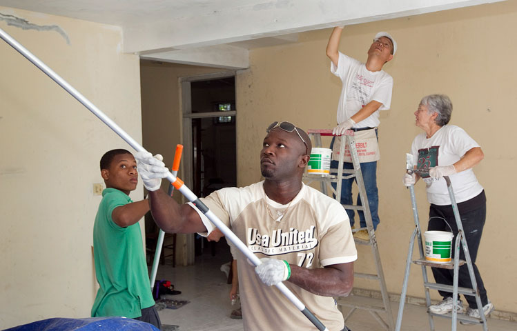"""Haitian and U.S. volunteers work together to paint the home of """"Sister Paulette"""" Holly at the Methodist Children's Home orphanage in Port-au-Prince, Haiti."""