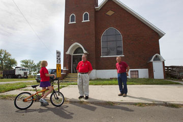 Ashley Kelley, 10, stops by the former Belmore (Ohio) United Methodist Church on her bicycle to ask the Rev. Tom Graves (center) and Ben Smith when the church might reopen. A UMNS photo by Mike DuBose.