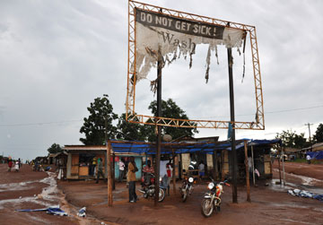 A torn billboard in the Yei District of South Sudan informs passersby of health alerts.