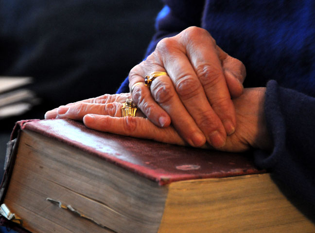 The Rev. Suzanne Field Rabb rests her hands on the family Bible.