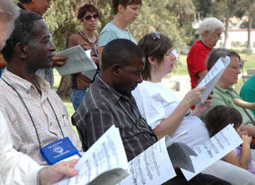 The Rev. Baamu Moses of Uganda, left, and the Rev. Copeland Nkhata from Malawi join others at the closing Shalom Summit worship service and lunch in L.A.'s MacArthur Park. A UMNS photo by Cate Monaghan.