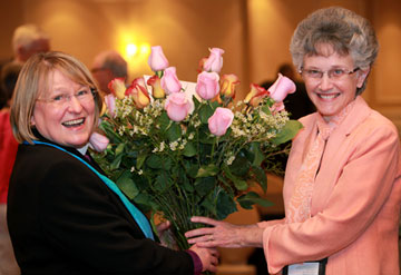 Bishop Wenner (left) receives roses from Bishop Peggy Johnson of the Philadelphia Area in congratulations of becoming the new president of the Council of Bishops.