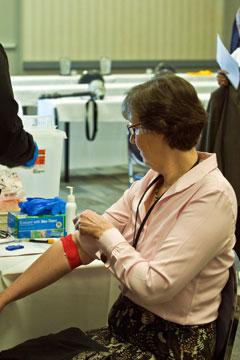 Denver Area Bishop Elaine Stanovsky rolls down her sleeve after being tested.