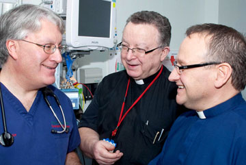 Moulton converses with the Rev. Neil Gray, Bolton's head chaplain and the Rev. Graham Culter, a British Methodist parish minister and Bolton chaplain.