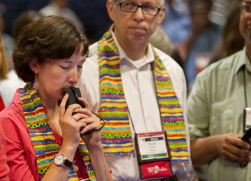 Delegate Sara Ann Swenson (left) of Minnesota presses her voting keypad to her lips while awaiting results of a vote on the United Methodist Church's stance on sexuality. A UMNS photo by Mike DuBose.