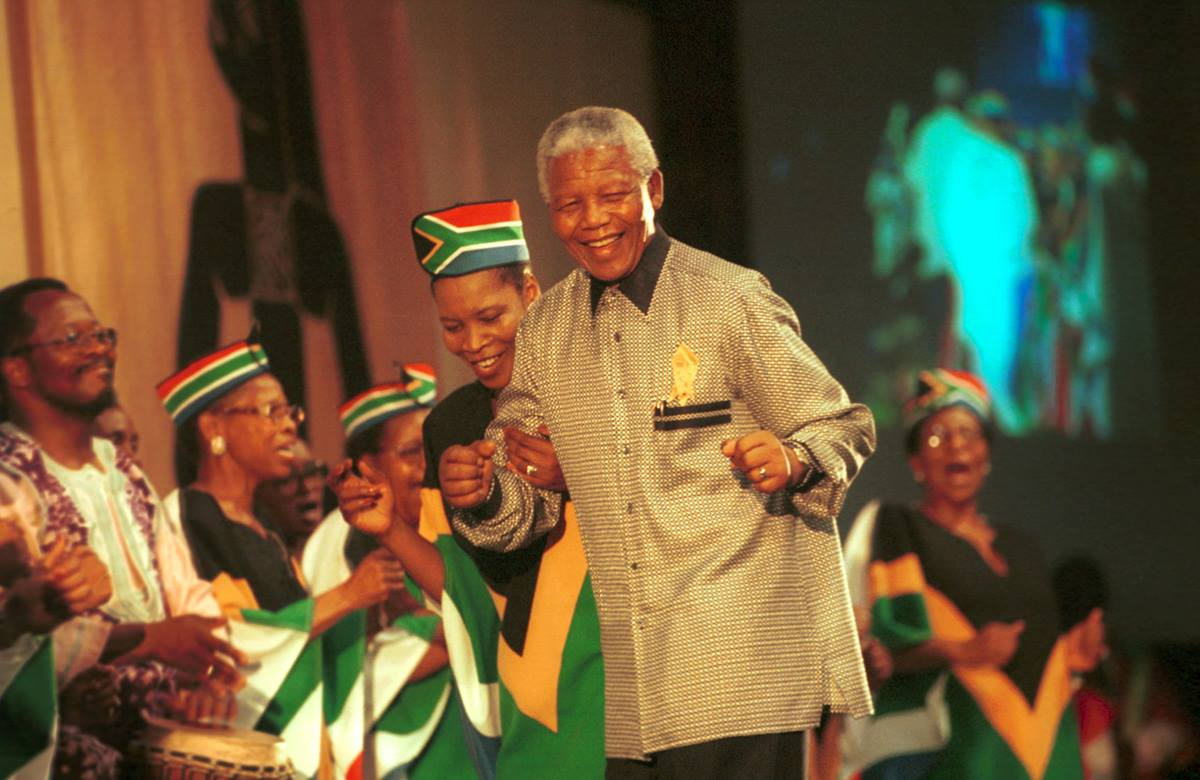 """Mandela is greeted at the 8th assembly of the World Council of Churches in Harare, Zimbabwe, in December 1998. """"Journey to Jubilee"""": South African Choir Photo by Chris Black/WCC."""