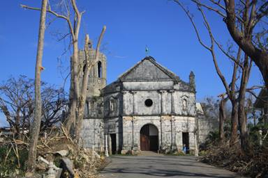 A church stands amidst the ruins caused by Typhoon Haiyan in the village of Daanbantayan, northern Cebu, Philippines. A UMNS photo by Ray Buchanan.