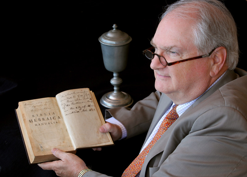 Robert J. Williams is retiring as top executive of the Commission on Archives and History. He's shown here holding a Bible and wearing glasses owned by Francis Asbury and with a communion chalice used by Philip William Otterbein. Asbury and Otterbein are important early figures in Methodist history.  A UMNS photo by Kathleen Barry