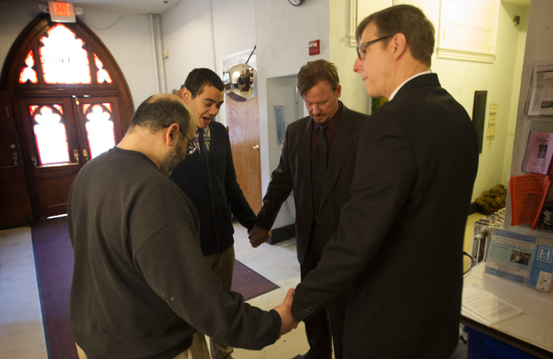 The Rev. Frank Schaefer (second from right) prays with supporters before a news conference at Arch Street United Methodist Church in Philadelphia where he announced he will not surrender his clergy credentials. Clockwise from front left are: Joe Kalil, Jordan Harris, Schaefer and the Rev. Robin Hynicka, pastor of the Arch Street church. A UMNS photo by Mike DuBose.