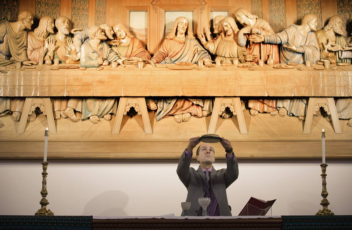 """The Rev. Edgardo Colón-Emeric blesses the elements of Holy Communion in front of a woodcarving of Leonardo da Vinci's """"The Last Supper"""" at the Upper Room Chapel in Nashville, Tenn. A UMNS photo by Mike DuBose."""